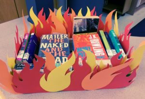 A display of banned books in a fake bonfire.