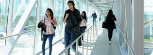 photo of students walking through glass covered overpass
