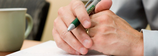 Hand resting on notebook holding pen