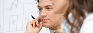 Young man holding a pen close to his head, thinking
