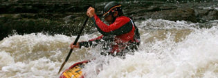 A male whitewater kayaker in some white water