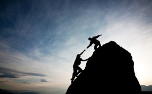 A silhouette of a person on a cliff reaching for another person on the top of the cliff - mentorship