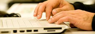 Closeup of hands using a laptop